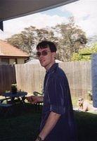 Gavin in the backyard of the old house, early 2003 I think. I don't know who that is sunbaking -- David, is that you?